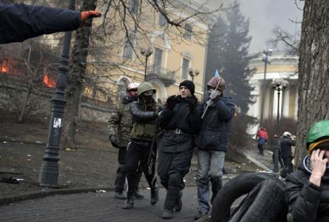 """Một viên cảnh sát bị phe biểu tình bắt làm """"tù binh"""" hôm 20/2. Hàng trăm người biểu tình có vũ trang đã đột kích vào chiến lũy cảnh sát trên quảng trường Độc lập. Những người biểu tình đã đẩy lui cảnh sát 200m và kiểm soát hầu hết quảng trường (Getty Images)"""